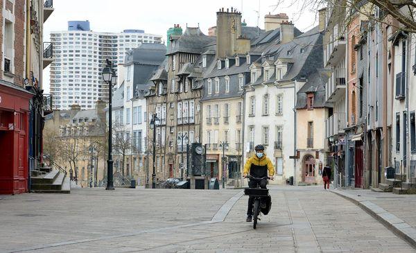 Un homme masqué fait du vélo dans le centre-ville de Rennes presque vide depuis l'application du confinement -  02/04/2020