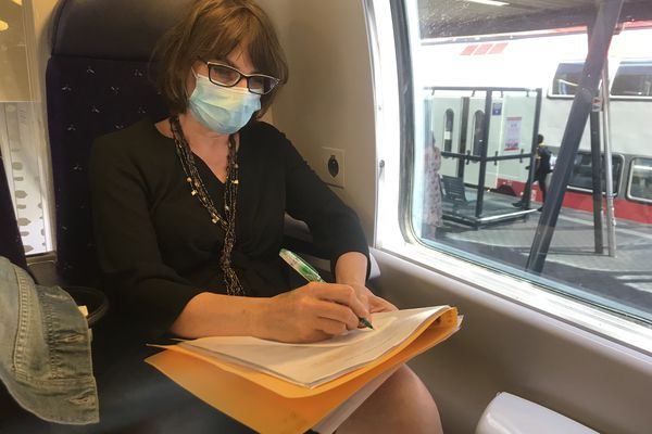 Cathie, une Messine enseignante de français au Luxembourg, corrige ses copies dans le TER.
