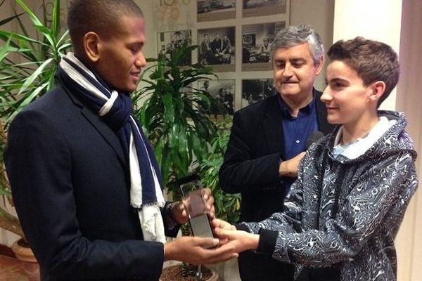 Joris Bouchaut recevant son trophée des mains de Charlie Guillaume sous les yeux de Carlos Bélinchon de France 3