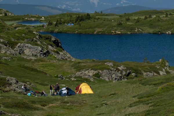 Des randonneurs campent en pleine journée sur le plateau des lacs dans le massif du Taillefer. Le bivouac est toléré, uniquement la nuit et à condition de respecter certaines règles.