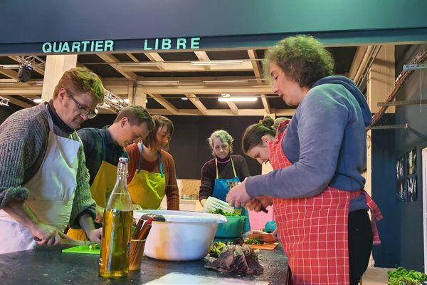 """Une équipe de bénévoles de l'association """"les bons restes"""" en pleine préparation d'un repas servi dans leur cantine solidaire éphémère à Quartier libre à Reims."""