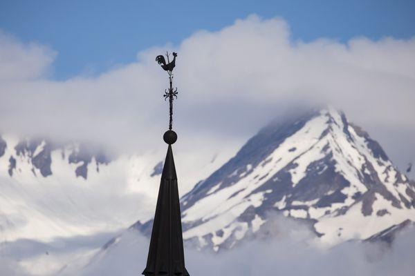 La girouette de l'église de Montvalezan (Savoie) devant les sommets enneigés de la Tarentaise le 16 mai 2020.