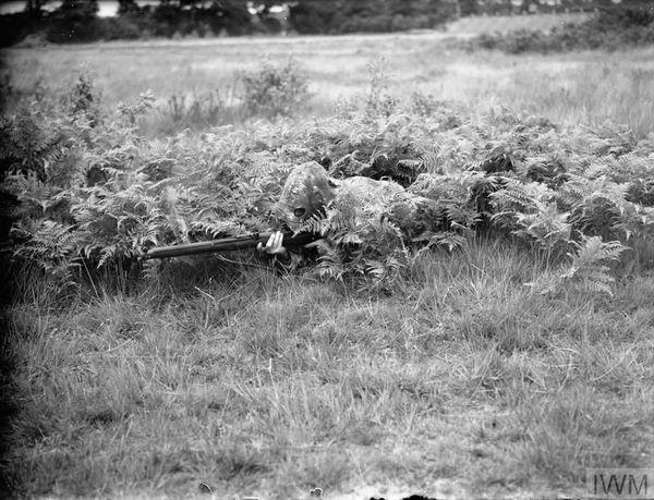 Un soldat britannique camouflé, à l'entraînement dans le Surrey (sud de l'Angleterre), le 9 juillet 1940.