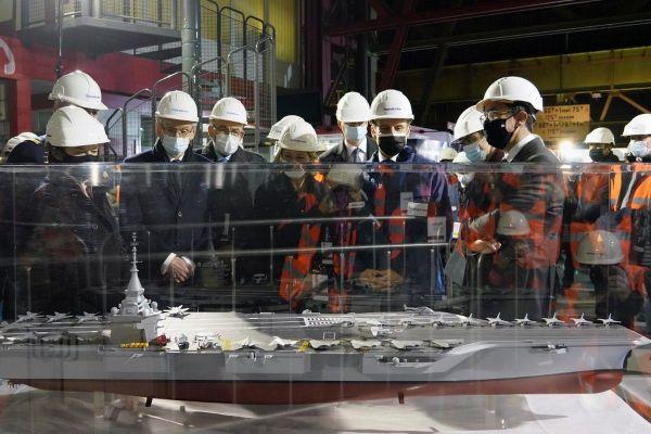 Le président Emmanuel Macron, en visite sur le site du groupe Framatome au Creusot, devant la maquette du futur porte-avions français.