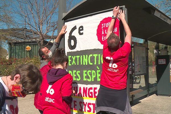 A Nîmes, les militants d'Attac recouvrent symboliquement les publicités à un arrêt de bus.