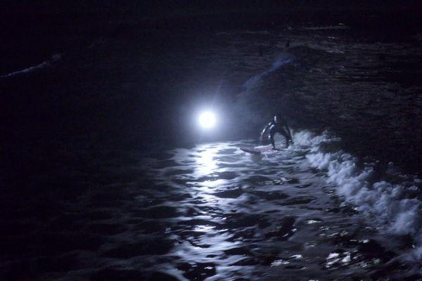 Des Surfeurs sous la pleine lune