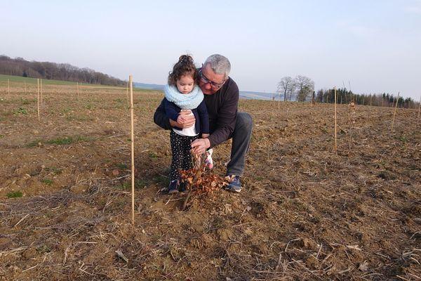 Pascal Lallemant et sa petite-fille, Charlotte, sur la parcelle où va se développer la forêt solidaire.
