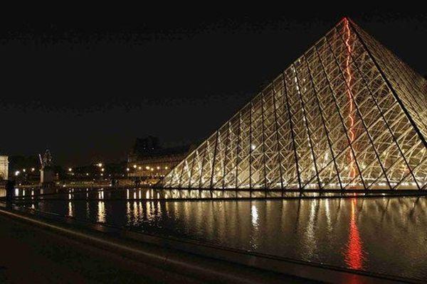 Un éclair rouge conçu par l'artiste nivernais Claude Levêque traverse la pyramide du Louvre