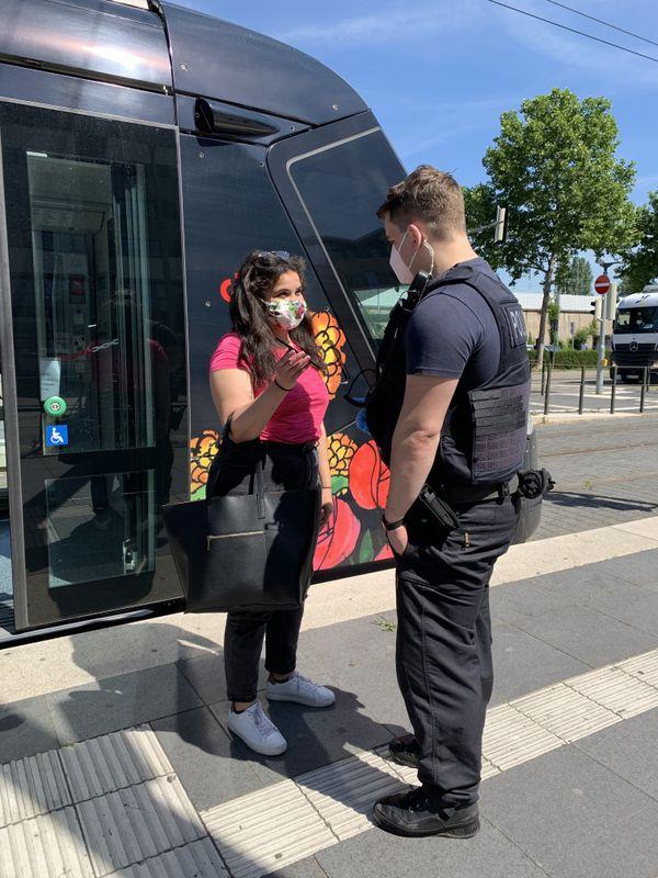 Nadia montre la photo de son passeport allemand sur son smartphone à un policier en sortant du tram