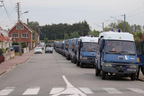 Des dizaines de cars de CRS sécurisent la zone lors du démantèlement d'un camp de plusieurs centaines de migrants à Calais, vendredi 4 juin 2021.