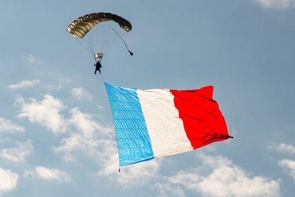 Un drapeau tricolore immense traverse le ciel de Luxeuil, emmené par l'équipe de parachutisme