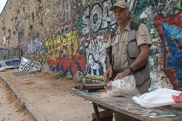 """Le géologue Michel Villeneuve, sur le boulodrome tout près du site antique avec une """"pierre-échantillon"""""""