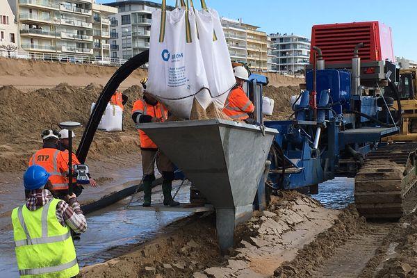 La machine en bleu creuse un sillon dans lequel le tuyau noir est enfoui et recouvert de sable adapté  à la plage