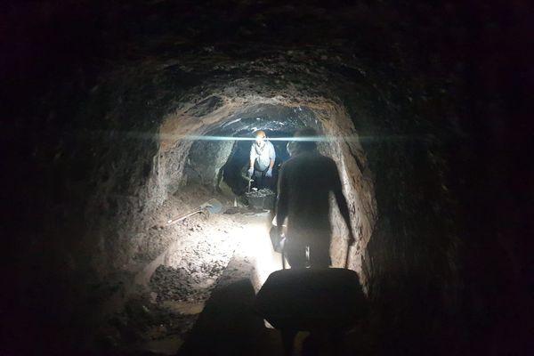 A la frontale, les bénévoles évacuent le limon, le long des 200 m du tunnel