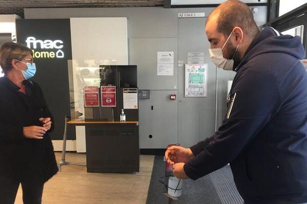 À l'entrée de ce magasin, une hôtesse accueille les clients pour s'assurer qu'ils portent un masquent et se désinfectent les mains.