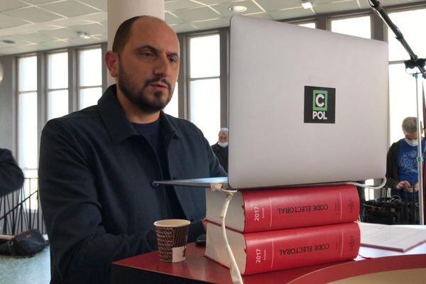 """Le présentateur de """" C Politique"""", Karim Rissouli, en visioconférence avec les chroniqueurs de l'émission. Son ordinateur portable est rehaussé grâce à deux tomes du code électoral !"""