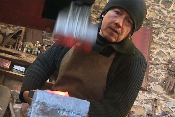 """Le sculpteur Morgan au travail au """"martinet"""" dans son atelier de forge dans l'Orne."""
