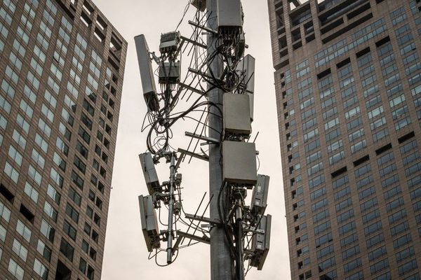 Un mât constellé de relais 5G dans une rue de Pékin
