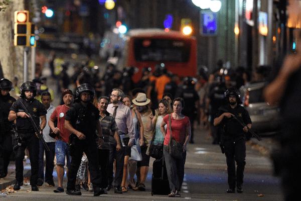 Des policiers espagnols raccompagnent les clients d'un magasin après un attentat sur les Ramblas qui a fait 13 morts et 80 blessés à Barcelone jeudi 17 août 2017