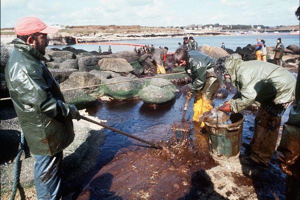 Avril 1978, des équipes tentent de nettoyer les rochers souillés par le pétrole de l'Amoco Cadiz