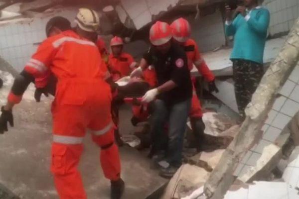 Les équipes de secours sortent une victime des décombres d'un immeuble, en Indonésie.