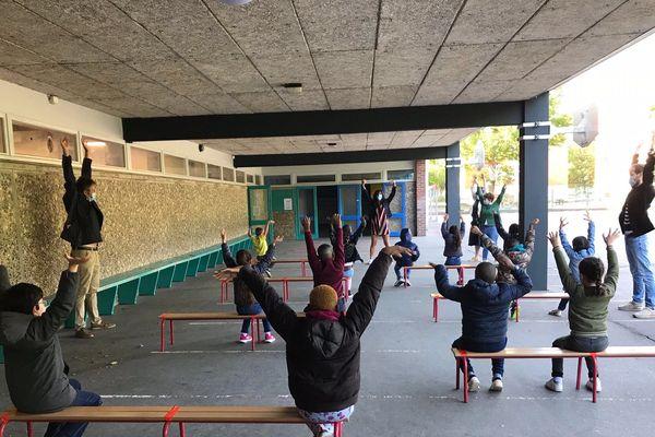 Sous le préau, on écarte les bras pour s'habituer à la bonne distance à l'école Clément Marot à Rouen
