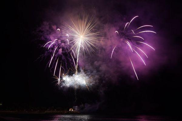 Le reflet des feux d'artifice est visible dans la mer.
