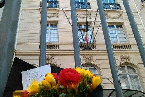 """Des fleurs devant l'ambassade de Belgique à Paris, drapeau en berne. Le président de la République a annoncé que les drapeaux seront mis """"en berne"""" en France jusqu'à  vendredi alors que la tour Eiffel prendra les couleurs du drapeau belge."""
