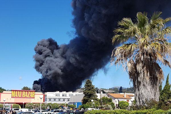 Un épais nuage de fumée noire s'échappe de l'incendie
