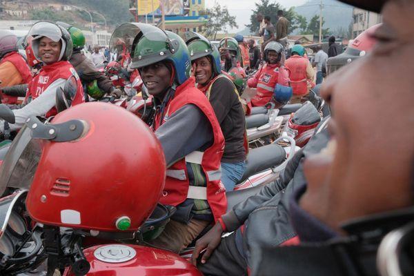 Des moto-taxis circulent dans le quartier central des affaires de Kigali. La culture du mototaxi a permis à des dizaines de milliers de Rwandais de devenir de petits entrepreneurs. La législation impose l'utilisation de casques de moto par tous les coureurs. Le gouvernement veut maintenant convertir la mototaxi à essence en mototaxi électrique.