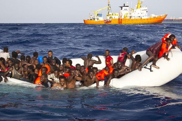 Les migrants secourus par SOS Méditerranée dans une mer agitée à bord d'une embarcation à moitié dégonflée, remplie d'eau et au moteur hors d'usage.