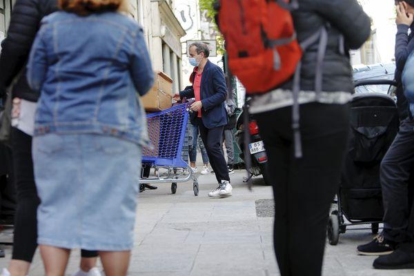 Des bénéficiaires du Secours Populaire font la queue sur le trottoir de la rue vernier à Nice, le 3 mai 2020.