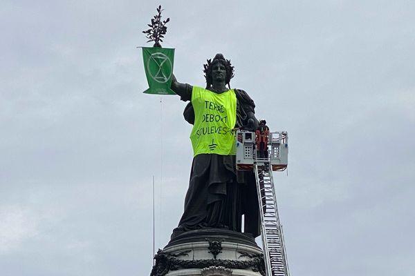 Les pompiers tentent tant bien que mal de retirer le gilet jaune que des activistes d'un collectif ont déposé sur la Marianne vendredi soir, place de la République.