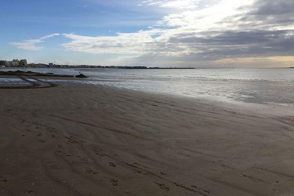 Au premier plan, un sable mat et compact car drainé par des chaussettes filtrantes enfouies sous la plage