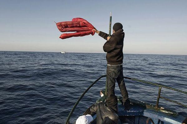 PiscitelliMigrants_002  Canal de Sicile, mer Méditerranée, 2 avril 2011. Un bateau transportant plus de 100 migrants en provenance de Tunisie fait signe à un bateau de pêche égyptien pour demander la direction de la côte italienne.© Giulio Piscitelli / Contrasto / Réa