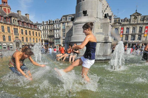 Des personnes se rafraichissent sur la Grand Place de Lille, il est 18 heures et le thermomètre affiche 39 degrés au soleil. C'était le 26 juin 2011.