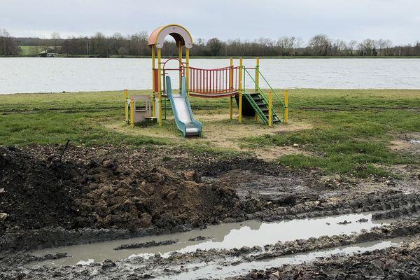 L'aire de jeu, au bord du plan d'eau, est désertée.