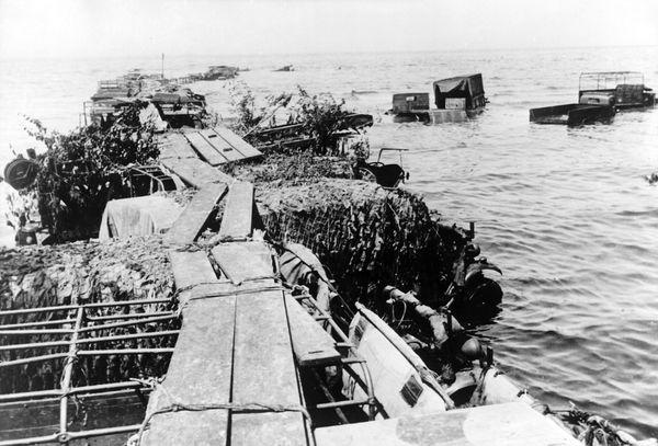 Des véhicules militaires sont utilisés pour créer des jetées de fortune permettant, à marée haute, l'évacuation des soldats depuis les plages.