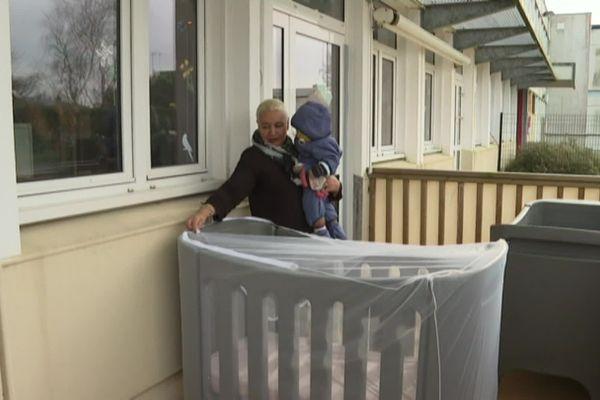 Malika installe un des bébés de la crèche pour une sieste en extérieur