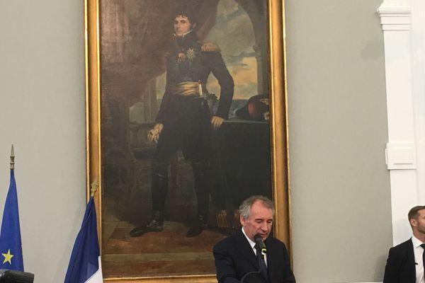 François Bayrou sous le portrait du roi de Suède originaire de Pau : Jean-Baptiste Bernadotte. Lors du discours officiel de réception de la famille royale.