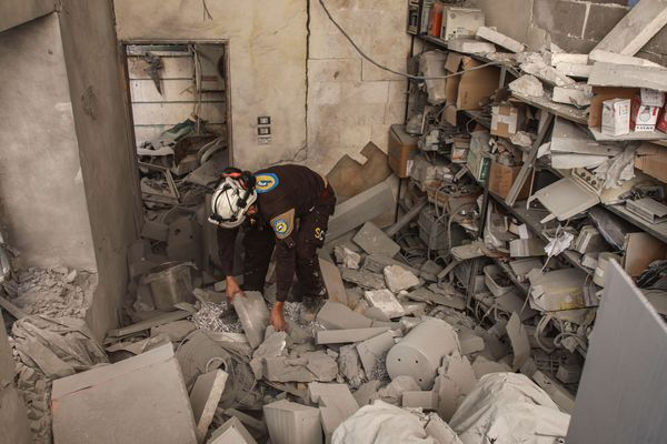 Un membre de la Défense civile syrienne fouille les débris et les décombres lors de la recherche de survivants dans un hôpital détruit dans la ville de Darret Ezza, à environ 30 kilomètres au nord-ouest de la ville syrienne d'Alep, dans le nord de la Syrie, le 17 février 2020.