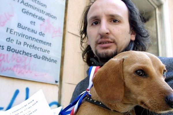 """Serge Scotto, auteur de polars marseillais, pose avec son chien """"Saucisse"""", le 01 mars 2001 devant la préfecture de Marseille, avant de déposer sa liste pour les élections municipales."""