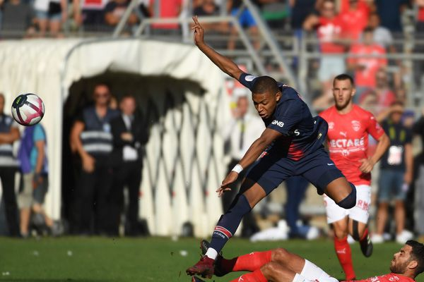 Kylian Mbappé sautant par-dessus Téji Savanier, le joueur nîmois à l'origine d'un tacle dangereux sur l'attaquant parisien dans les arrêts de jeu, menant à l'expulsion de ce dernier (Nîmes - PSG, 2-4, 01/09/2018).