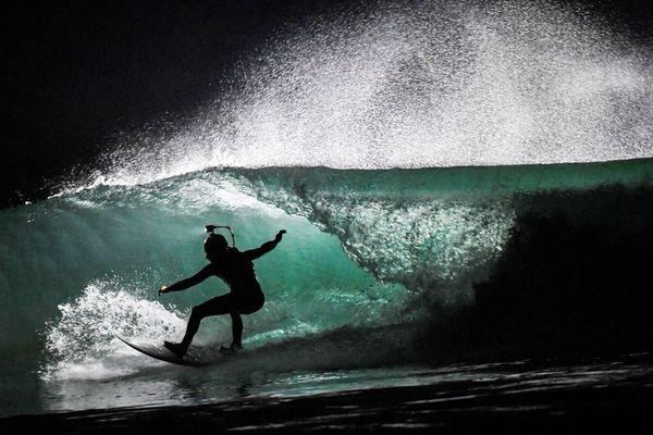 Un surfeur de nuit au Cap Frehel à Plevenon