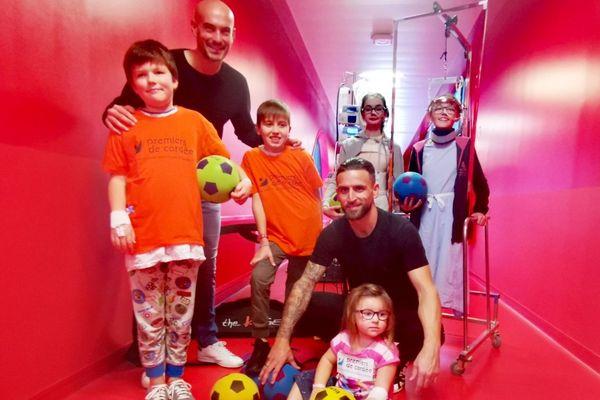 """Rémy Riou ( à gauche) et Anthony Gonçalves du Stade Malherbe Caen, tout sourire, avec les enfants qui ont joué avec eux dans les couloirs du CHU, dans le cadre de l'opération """"sport à l'hôpital"""""""