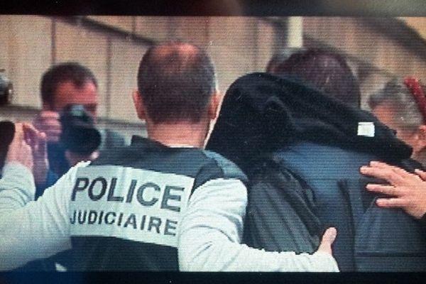 Le principal suspect arrive au tribunal sous escorte.