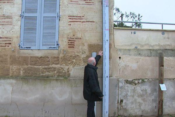 Le maire de Couthures-sur-Garonne montrant le niveau de la dernière crue (8,50).