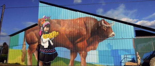 Petite fille avec fleurs - Fresque de Mako Moya sur bâtiment agricole à Saint-Pierre-Chérignat en Creuse