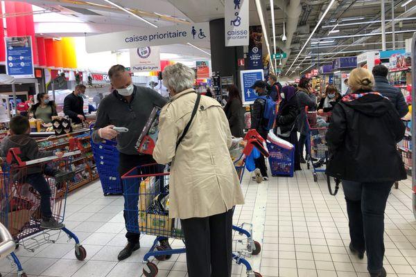Des clients font leurs courses dans les allées du supermarché Carrefour Ile Napoléon à Illzach.