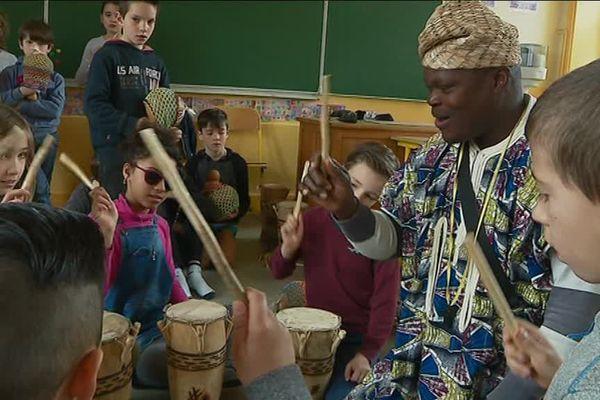 Les membres de la fanfare Olaïtan apprennent aux enfants à taper en rythme.